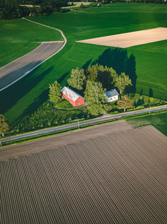 Aerial view of farmland with red barn and houses and harvest field in rural Finland