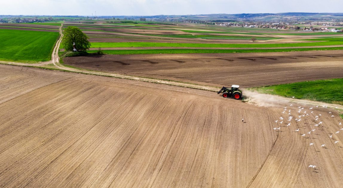 Tracktor Working in Fields at Countryside Farm. Aerial Drone View.